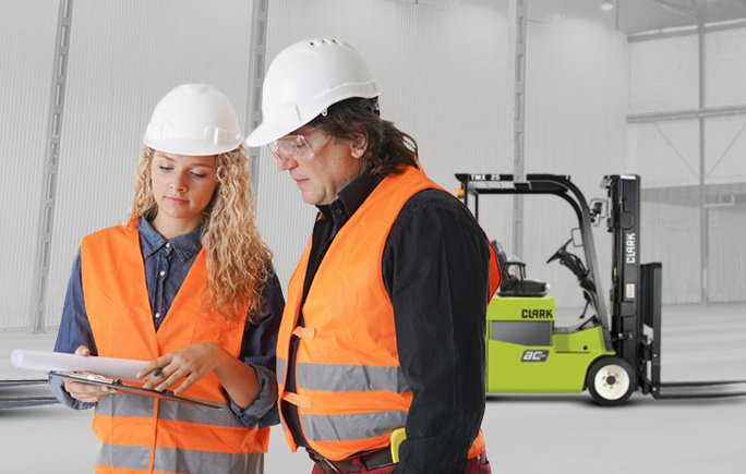 Instructor reviews safety guidelines with forklift operator